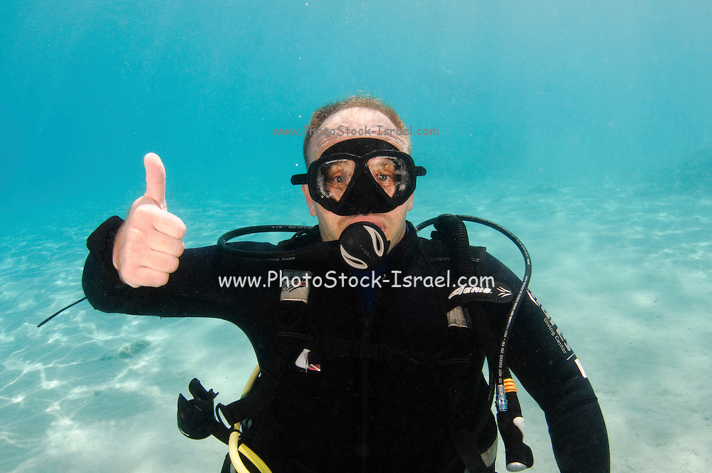 Underwater Hand signs scuba diver demonstrates the sign language for divers. Ascend, or I am going up: A fist is made with one hand, thumb extended upward, and hand is moved upward to emphasize direction of travel.