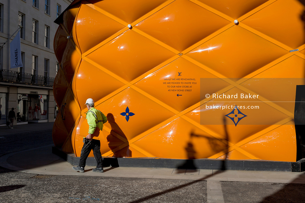 A construction workman carries part of the temporary renovation hoarding of luxury brand Louis Vuitton in New Bond Street, on 25th February 2019, in London, England.