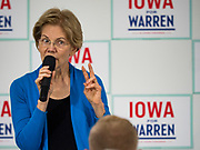 """26 NOVEMBER 2019 - KNOXVILLE, IOWA: US Senator ELIZABETH WARREN (D-MA) holds up two fingers while talking about her proposed two percent """"wealth tax"""" to a crowd of about 90 people during a campaign event in Knoxville Tuesday. Sen. Warren hosted a community meeting at the Sprint Car Hall of Fame and Museum in Knoxville, IA. She is running to be the Democratic candidate for the US Presidency in the 2020 election. Iowa hosts the first selection event of the presidential election season. The Iowa caucuses are February 3, 2020.                    PHOTO BY JACK KURTZ"""