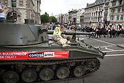 Tank passed through Parliament Square as members of the Life Guards cavalry passes. Campaigners and supporters from Oxfam and Amnesty International, as part of the Control Arms coalition, drive an Abbot gun tank around central London to highlight the need for a global Arms Trade Treaty (ATT) to be agreed during a United Nations conference next month (July 2012). London, England, UK. 27th June 2012.