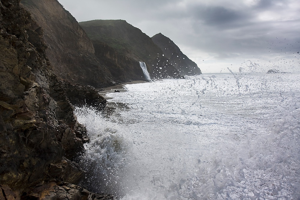 Waves crash into the rugged rocky coastline, spraying foam into the air, at Wildcat Beach, Point Reyes National Seashore, California. The steep cliffs render the beach dangerous or unaccessible at high tide. Alamere Falls is visible in the background.