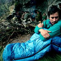 TIBET, CHINA. Tsangpo River Gorge, David Breashears wakes to rain in Himalayan cave below Mt.Namche Barwa (porters bkg).