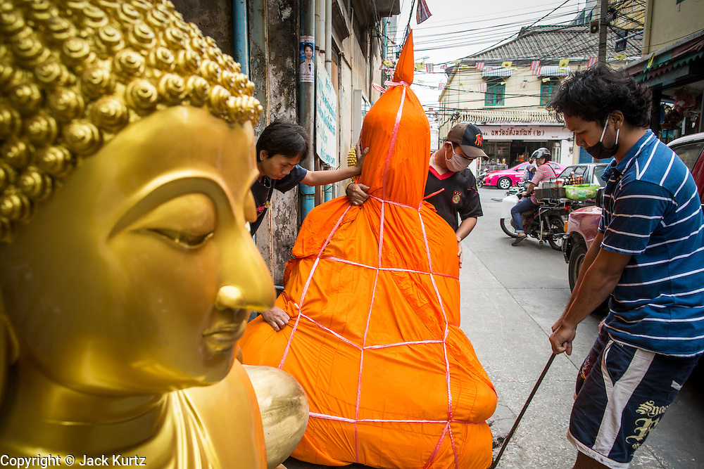 """12 NOVEMBER 2012 - BANGKOK, THAILAND:   Men bring a sold statue of the Buddha out to a waiting delivery truck on Bamrung Muang Street in Bangkok. Buddhas are covered in saffron when they are moved. Thanon Bamrung Muang (Thanon is Thai for Road or Street) is Bangkok's """"Street of Many Buddhas."""" Like many ancient cities, Bangkok was once a city of artisan's neighborhoods and Bamrung Muang Road, near Bangkok's present day city hall, was once the street where all the country's Buddha statues were made. Now they made in factories on the edge of Bangkok, but Bamrung Muang Road is still where the statues are sold. Once an elephant trail, it was one of the first streets paved in Bangkok. It is the largest center of Buddhist supplies in Thailand. Not just statues but also monk's robes, candles, alms bowls, and pre-configured alms baskets are for sale along both sides of the street.    PHOTO BY JACK KURTZ"""
