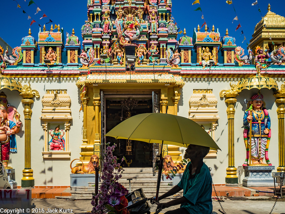 17 NOVEMBER 2016 - GEORGE TOWN, PENANG, MALAYSIA:  A pedicab driver stopped in front of the entrance to the Sri Mahamariamman Hindu Temple in George Town, Penang, Malaysia. George Town is a UNESCO World Heritage city and wrestles with maintaining its traditional lifestyle and mass tourism.       PHOTO BY JACK KURTZ