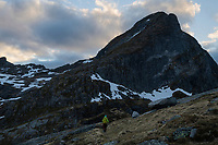Female hiker on faint trail towards Narvtind mountain peak, Moskenesøy, Lofoten Islands, Norway