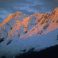 First light from the pokes through a cloud to illuminate the glaciers and icefalls on 5936-meter Nevado Sacsarayoc in the Cordillera Vilcabamba range of Peru's Andes Mountains.