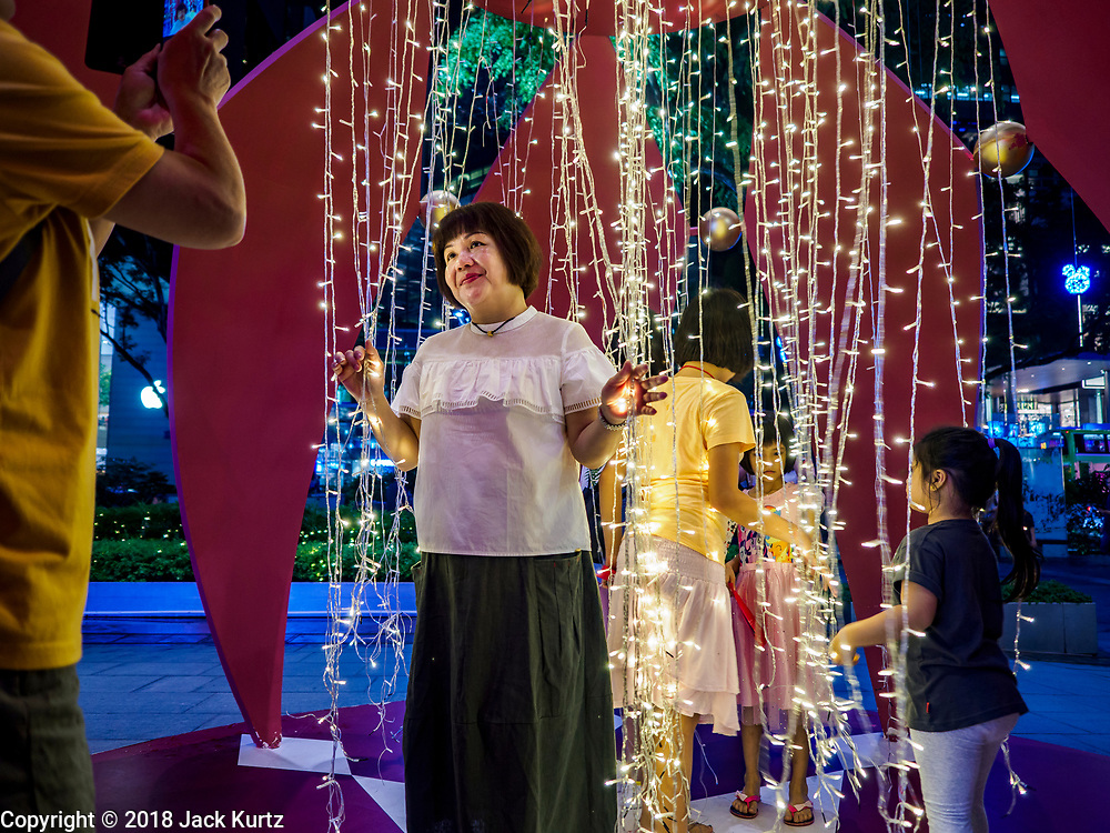 """12 DECEMBER 2018 - SINGAPORE:  A woman poses for pictures in a display that resembles Christmas ornaments on Orchard Road. Orchard Road is the main shopping district of Singapore and for years hosts a large light display around Christmas. The main sponsor of this year's display is the Disney Company and the displays are decorated with characters from the Disney entertainment universe. This has upset some religious leaders in Singapore and the National Council of Churches of Singapore (NCCS) sent a letter to the Singapore Tourism Board (STB) expressing its concern about the """"increasing secularisation and commercialization of Christmas"""" in Singapore. The STB reached out to the NCCS, but the Orchard Road lights will remain on through the holidays.  PHOTO BY JACK KURTZ"""