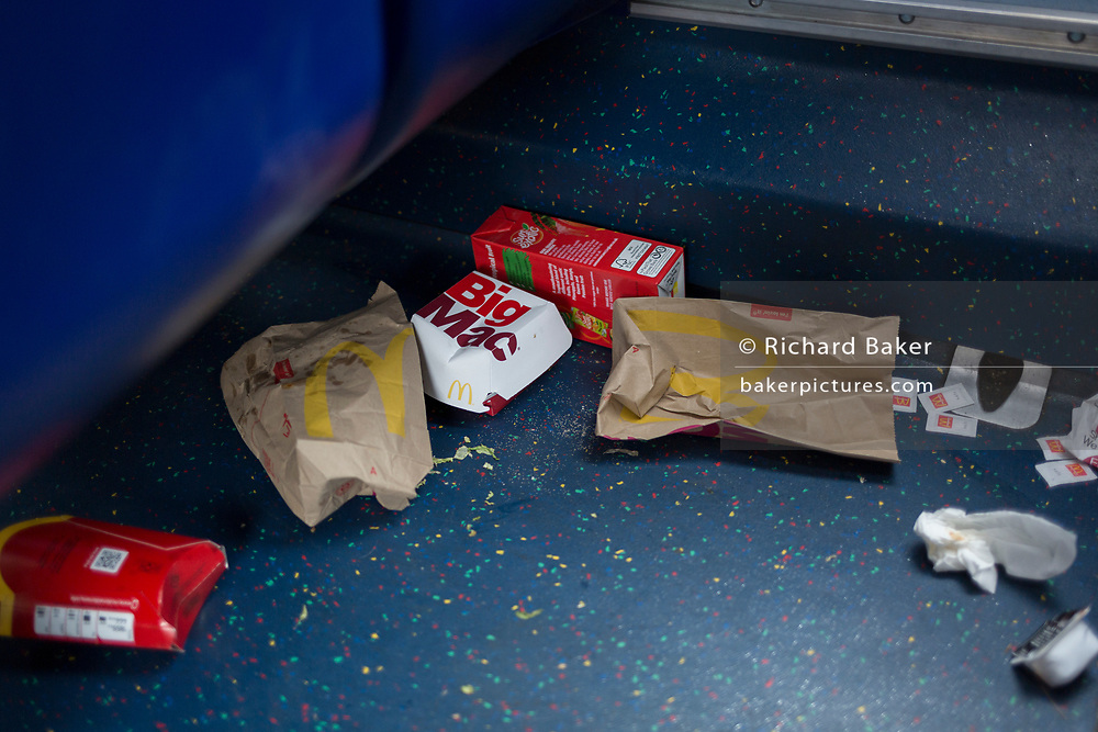 Dropped McDonalds packaging and food remains on the floor of a London bus, on 3rd October 2019, in south London, England