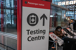 © Licensed to London News Pictures. 08/01/2021. London, UK. A passenger sits next to a Covid-19 Testing Centre sign at London Heathrow as Mayor of London, Sadiq Khan declares a Major Incident as cases continue to spread throughout the capital. This week, Prime Minister Boris Johnson plunged England into a 3rd lockdown as he ordered schools to close and workers to work from home as the government brings in the army to ramp up vaccinations across the country. Photo credit: Alex Lentati/LNP