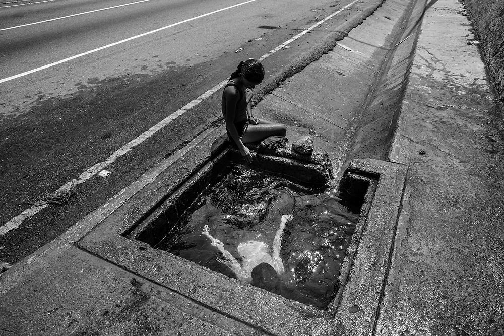 Niños juegan y se bañan en una alcantarilla de agua insalubre en una autopista, el 11 de noviembre del 2020 en Caracas, Venezuela. Aproximadamente desde hace 5 años, los venezolanos padecen de falta de agua. Los ciudadanos responsabilizan a los gobernantes de la precariedad del servicio, mientras que las autoridades acusan a ataques terroristas de sabotear el servicio. La gran mayoría de venezolanos no tienen servicio de agua potable en sus casas, paradójicamente esto ocurre en el 10 país del mundo con las mayores reservas de agua dulce de todo el planeta.