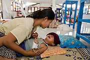 """23 FEBRUARY 2008 -- MAE SOT, TAK, THAILAND: Ti Su Wa, a 2 year old Karen boy and his mother in the pediatrics ward at the Mae Tao Clinic in Mae Sot, Thailand. There are no beds in the ward, the children (and their parents) sleep on bamboo sleeping mats they bring with them. The clinic treated more than 80,000 people in 2007, all Burmese. Most of them are living illegally in Thailand, but many come to the clinic from Burma because they either can't afford medical care in Burma or because it isn't available to them. There are millions of Burmese refugees living in Thailand. Many live in refugee camps along the Thai-Burma (Myanmar) border, but most live in Thailand as illegal immigrants. They don't have papers and can not live, work or travel in Thailand but they do so """"under the radar"""" by either avoiding Thai officials or paying bribes to stay in the country. Most have fled political persecution in Burma but many are simply in search of a better life and greater economic opportunity.  Photo by Jack Kurtz"""