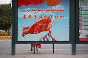 Xinjiang, China. «Fly high the flag of national unity», reads a propaganda billboard on a busstop Kashgar, the capital of the Uighurs.<br /> To get support from the population for their modernization programme, the authorities want to highlight the greatness of the country with those kind of propaganda posters. NATACHA DE MAHIEU