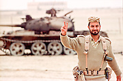 A Qatar soldier walking past a destroyed Iraqi tank flashes the victory sign during clean up operations following the Battle of Khafji February 2, 1991 in Khafji City, Saudi Arabia. The Battle of Khafji was the first major ground engagement of the Gulf War.