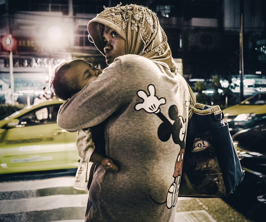 Muslim woman holding her child near  Sukhumvit Soi 3/1 or Soi Arab in Bangkok with many visitors of arabic countries