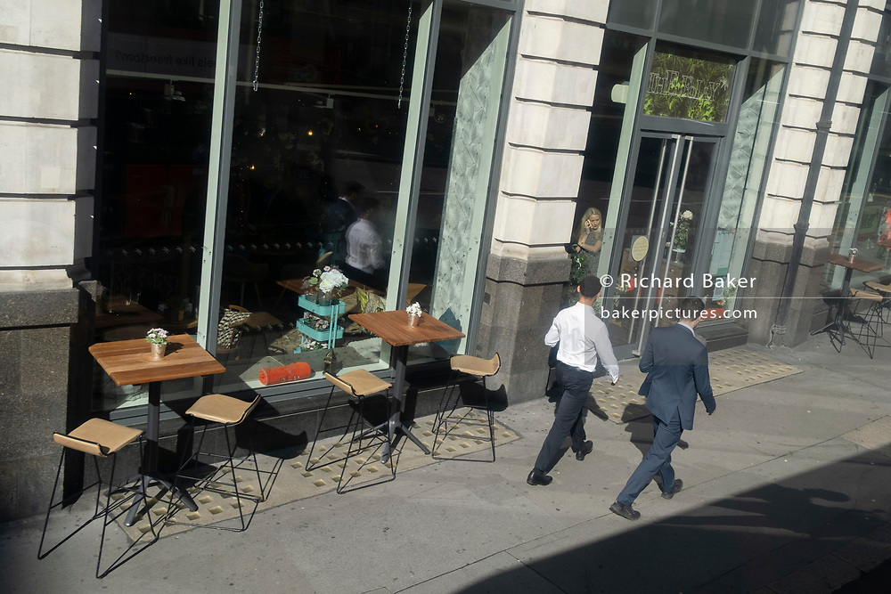 Two City businessmen walk past a bar where a woman is speaking on her phone, on 5th October 2020, in London, England.