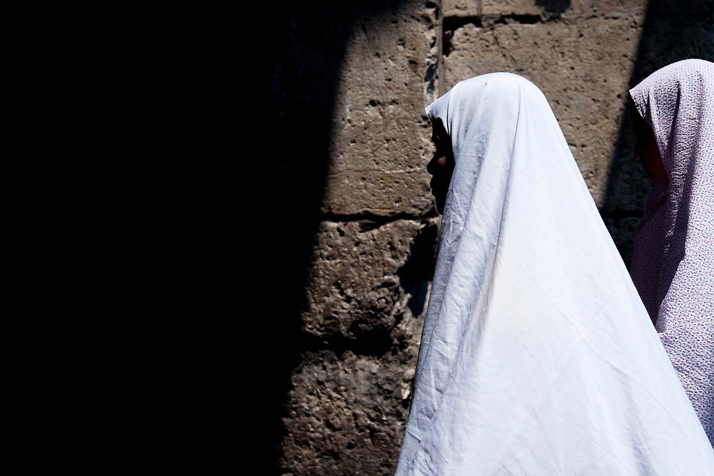 Palestinian women make their way through Jerusalem's Old City to attend prayers at the Al Aqsa Mosque on the first Friday of the Muslim holy month of Ramadan, on August 13, 2010.