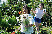 Its Friday morning, and a bride, her maid of honour, bridesmaid and Mum pick local British Flowers for a wedding the following day<br /><br />Jen is the owner at 'Blooming Green Flowers'. She runs the farm with her partner Bek. Blooming Green Flowers is a British flower farm is near Marden Kent, south of Maidstone, not far from London. Wedding parties come to collect their flowers, typically on a Thursday, Friday or Saturday morning. In the summer, on Friday afternoons families, everyone, from the very young to old come to pick flowers. Cost £10 a container.<br /><br />British local flowers, grown nearby, count for around 10% of the UK market, traveling less than a tenth of their foreign counterparts which are often flown in from abroad. Nearly 90% of the flowers sold in the UK are actually imported, and many travel over 3000 miles. Local flower farms help biodiversity, providing food and habitat to a huge variety of wildlife, insects including butterflies, bugs, and bees. Often local flower farmers prefer to grow organic rather than using pesticides. British flowers bloom all the year around, even in the depths of winter, and there are local flower farms throughout the country.<br /><br />Many people like the idea of the just picked from the garden look, and come to flower farms throughout Britain to pick their own for weddings, parties and garden fetes. Others come for the joy of a day out in the countryside with their family. Often a bride and her family will come to pick the flowers for her own wedding, some even plant the seeds earlier in the year.