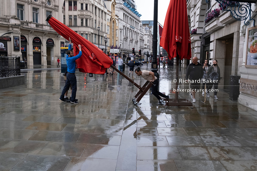 The tipping point angle is reached as a team of three employees of a bar, push and pull a second tall canopy of their street business on a wet Piccadilly Circus pavement, on 18th June 2021, in London, England.