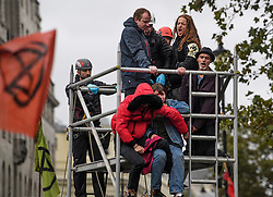 © Licensed to London News Pictures. 07/10/2019. London, UK. A group of specialist police officers remove Extinction Rebellion activists from a scaffolding structure in Trafalgar Square in Westminster. Activists plan to converge on Westminster blockading roads in the area for at least two weeks calling on government departments to 'Tell the Truth' about what they are doing to tackle the Emergency. Photo credit: Ben Cawthra/LNP