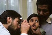 A young national Health general practitioner doctor (GP) uses an otoscope to inspect an even young little girl - a Tamil refugee from Sri Lanka whose father has brought his family to Britain in 1986 to escape racial and political persecution during his country's war between the Sinhalese majority and this ethnic minority group. The surgery is in the north London borough of Camden and the child of approximately 8 years of age is held by her father's firm hand that grips her chin to avoid movement. The health professional peers into the instrument to check for infections so the little girl can carry on dealing with this unfamiliar adopted country and strange ways of life in the UK.