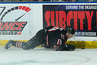KELOWNA, BC - FEBRUARY 17: Carson Focht #19 of the Calgary Hitmen falls to the ice after a second period check by the Kelowna Rockets at Prospera Place on February 17, 2020 in Kelowna, Canada. (Photo by Marissa Baecker/Shoot the Breeze)