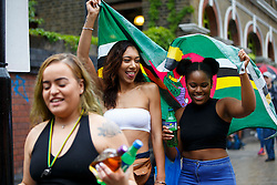 © Licensed to London News Pictures. 28/08/2016. London, UK. Spectators take shelter in the rain whilst watching the parade on family day of Notting Hill Carnival in west London, Sunday, 28 August 2016. Photo credit: Tolga Akmen/LNP