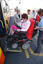 Wheelchair user with cerebral palsy getting on a bus using ramp.