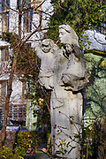 Stone sculpture of a mother holding two young children Bucharest, Romania.