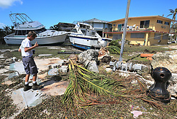 Lori Steller gives a thumbs up while inspecting her property on Tuesday, September 12, 2017, after two large boats washed onto her lot in Key Largo during Hurricane Irma storm surge. Photo by Al Diaz/Miami Herald/TNS/ABACAPRESS.COM