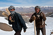 Rajab, right, 15, a villager from Jawzari, made his snowboard by nailing metal from cooking oil cans to a plank from a tree that he cut down himself.