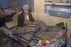 Man with disability lying in bed at the Apahaj Ashram; Patiala; Punjab; India,