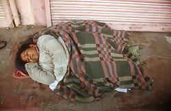 Homeless woman sleeping rough on the street in India,