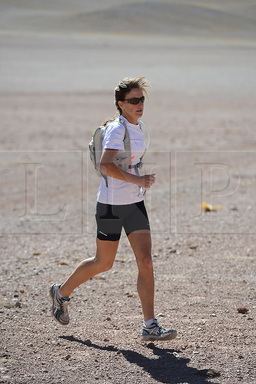 © Licensed to London News Pictures. 14/11/2013.<br /> <br /> British runner Yvonne Brown, bib no. 6, winner of the Ladies race.<br /> <br /> Inaugural Volcano Marathon, Atacama Desert, Chile. The race took place in the Atacama Desert in Chile, beginning at an altitude of 4,400 metres (14,500 feet) in the vicinity of Lascar Volcano. It was a gruelling affair for many of the competitors who had to encounter some challenging hills and manage the impact of the heat and oxygen deprivation. The average altitude of the entire race was close to 4,000 metres and temperatures reached the mid 20s Celsius, or almost 80 Degrees Farenheit.<br /> <br /> Photo credit : Mike King/LNP<br /> <br /> Further information and link to video here: https://www.dropbox.com/s/0277bepxvo0t8il/Marathon%20copy.txt