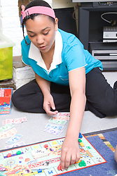 Teenaged girl playing a game of Monopoly on the floor at home,
