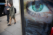A blind or partially sighted man walks past a Big Brother like eye looking out from a phone box in central London. The large scale eye looks as if it is keeping surveillance on passers by. UK.