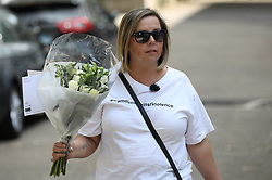 © Licensed to London News Pictures. 13/08/2019. London, UK. A woman brings flowers to the crime scene at Munster Square in Camden, North London, where a male was stabbed to death last night. The victim, whose age has not yet been released, was pronounced dead at the scene after police were called shortly after 11pm. Photo credit: Peter Macdiarmid/LNP