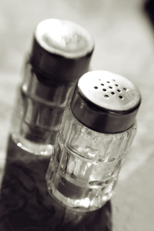 salt and pepper shaker standing on table,black and white verticle