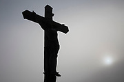 Crucifix in silhouette as the sun shines through the mist Saint-Cirq-Lapopie, France. Saint-Cirq-Lapopie is a commune in the Lot department in south-western France. It is a member of the Les Plus Beaux Villages de France The most beautiful villages of France association. Its position, originally selected for defense, perched on a steep cliff 100 m above the river has helped make the town one of the most popular tourist destinations in the department.