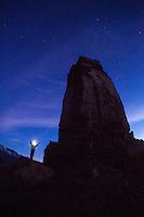 Woman doing yoga at night under Castleton Tower near Moab, UT. Castle Valley, UT.