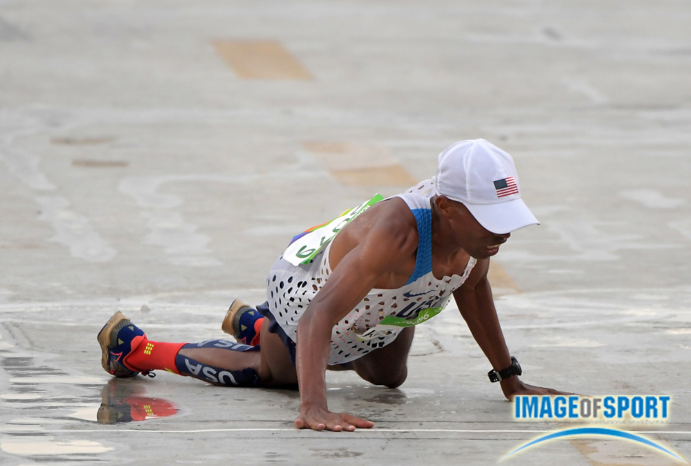 Aug 21, 2016; Rio de Janeiro, Brazil; Meb Keflezighi (USA) falls at the finish of the marathon during the Rio 2016 Summer Olympic Games at Sambodromo. Keflezighi placed 33rrd in 2:16:46.