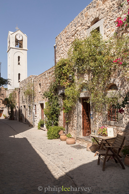 Quaint street with old building covered by creeping plant and clock tower, Mesta, Chios, Greece