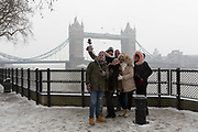 A group of tourists take a selfie photograph in front of Tower Bridge during snow fall in London, England on March 2nd, 2018 as freezing weather conditions dubbed the Beast from the East combined with Storm Emma have brought snow and freezing weather to the UK.