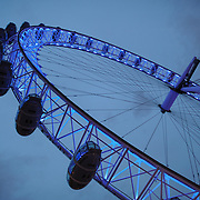 The London Eye (formerly known as the Millenium Wheel) at dusk against an overcast sky.