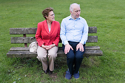 Older couple sitting on a park bench,
