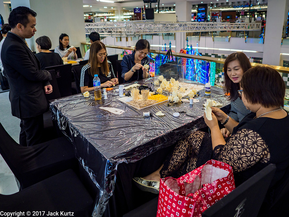 """24 MAY 2017 - BANGKOK, THAILAND: Volunteers at the Emporium, an upscale shopping mall in Bangkok, make wooden roses to be used during the cremation of Bhumibol Adulyadej, the Late King of Thailand. In Thai culture it is customary to place wooden flowers in front of a deceased person's coffin or urn as a last tribute before cremation. The Royal Cremation Organisation Committee, which is overseeing plans for the cremation of Bhumibol Adulyadej, the Late King of Thailand, asked the Bangkok Metropolitan Administration (BMA) to provide three million wooden flowers for the late King's cremation. The BMA, in turn, has asked malls and civic organizations to provide flowers. The Mall Group, which owns Emporium, has pledged to provide up to one million wooden """"Wiangping"""" roses, which in Thai culture symbolize unconditional love. The late King will be cremated October 26, 2017.     PHOTO BY JACK KURTZ"""