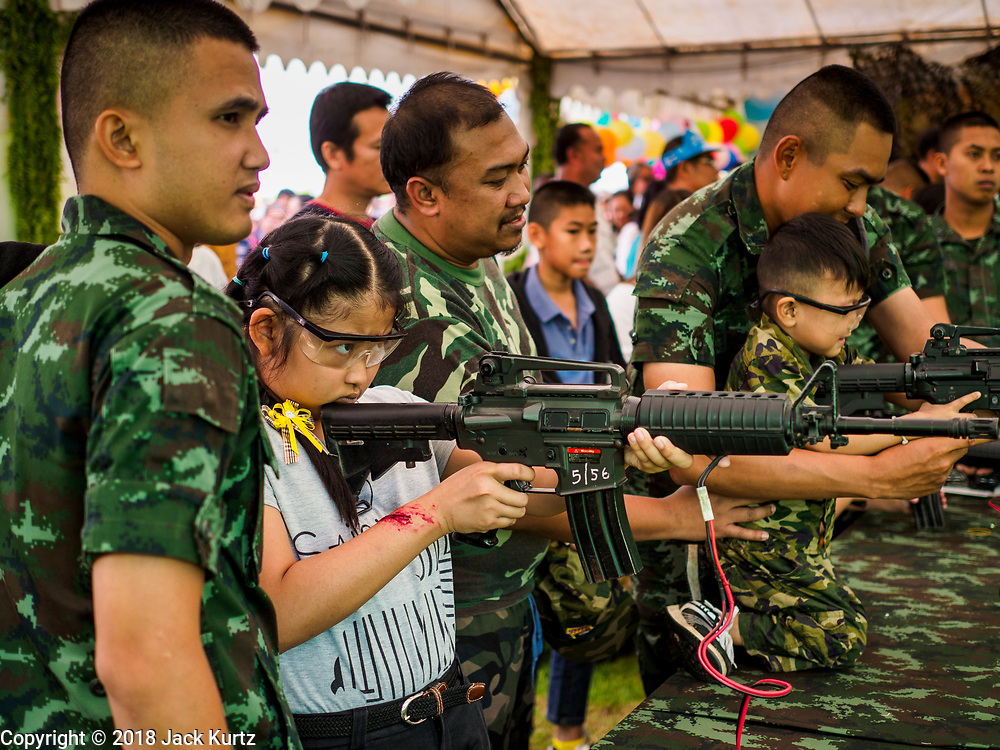 """13 JANUARY 2018 - BANGKOK, THAILAND:      A Thai child fires a BB gun that looks like a M4 assault rifle during Children's Day activities at the Royal Thai Army's King's Guard 2nd Cavalry Camp in central Bangkok. Children's Day is called """"Wan Dek"""" in Thai. Many government offices and military bases hold special activities for children as do shopping malls.  PHOTO BY JACK KURTZ"""