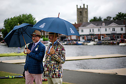 © Licensed to London News Pictures. 28/06/2017. London, UK. Two men shelter form light rain at Day one of the Henley Royal Regatta, set on the River Thames by the town of Henley-on-Thames in England.  Established in 1839, the five day international rowing event, raced over a course of 2,112 meters (1 mile 550 yards), is considered an important part of the English social season. Photo credit: Ben Cawthra/LNP