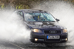 © Licensed to London News Pictures. 13/03/2021. Castleton, UK. A car drives through flood water in Castleton, High Peak, Derbyshire, following heavy rain overnight. Ioannis Alexopoulos/LNP
