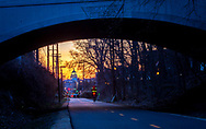 Lone cyclist pedals down the Southwest Commuter Bike Path, state Capitol at sunrise in the distance. Photo taken April 26, 2018.
