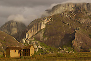 Betsileo house near Ambalavao town. South-central highlands of MADAGASCAR. Granite cliffs in background